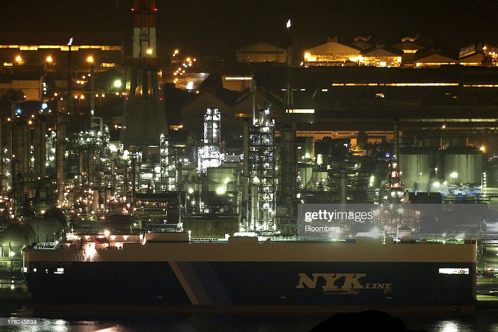 A Nippon Yusen K.K. vehicle transporter ship is moored at a port next to plants illuminated at night in the Mizushima coastal industrial complex in Kurashiki, Okayama Prefecture, Japan, on Monday, Aug. 26, 2013. Japan's top listed companies doubled earnings last quarter from a year earlier, exceeding already high forecasts and generating support for the economic recovery effort of Prime Minister Shinzo Abe. Photographer: Kiyoshi Ota/Bloomberg via Getty Images