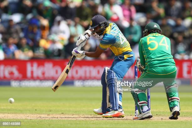 Niroshan Dickwella of Sri Lanka cuts to the offside as wicketkeeper Sarfraz Ahmed looks on during the ICC Champions Trophy match between Sri Lanka...