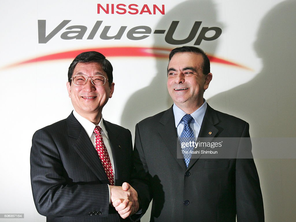 Nissan Motor Announces New COO Toshiyuki Shiga and president Carlos Ghosn shake hands during a press conference on February 21 2005 in Tokyo Japan