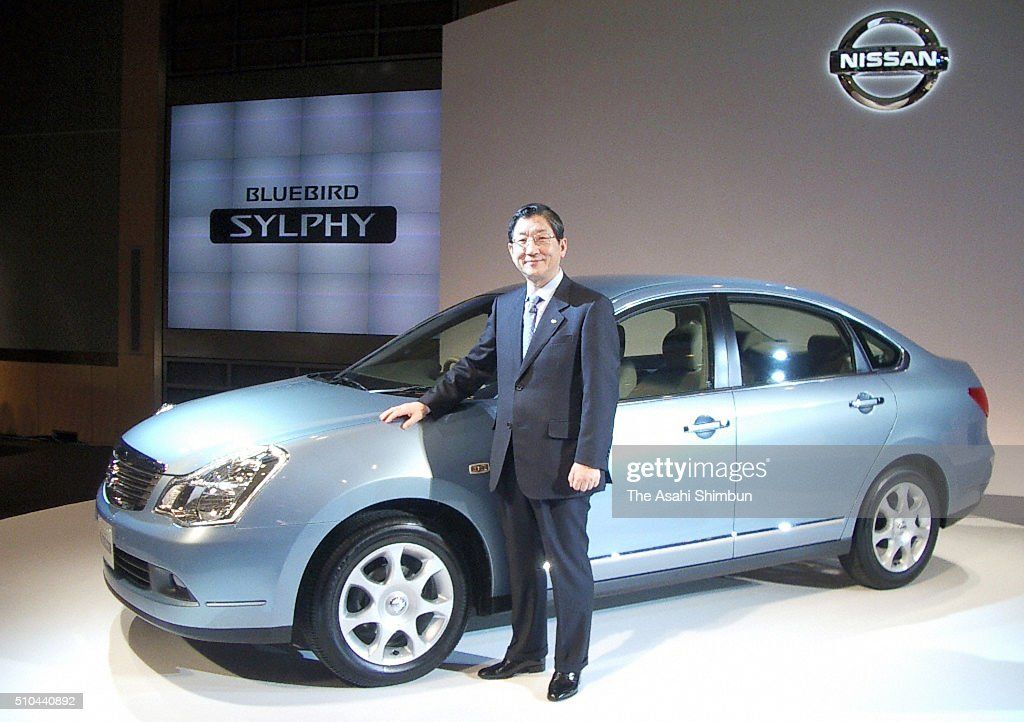 Nissan Motor Co COO Toshiyuki Shiga stands next to the company's new sedan 'Bluebird Sylphy' during its unveiling on December 21 2005 in Tokyo Japan
