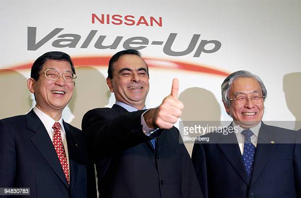 Nissan Motors President and Chief Executive Officer Carlos Ghosn center gives a thumbsup sign as Senior Vice President Toshiyuki Shiga left and...