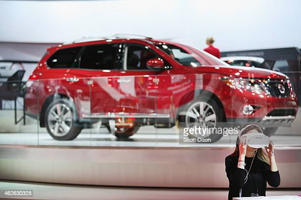Nissan Pathfinder sits on display behind a guest who is trying out Nissan's 1DX 3D Experience at the North American International Auto Show on...
