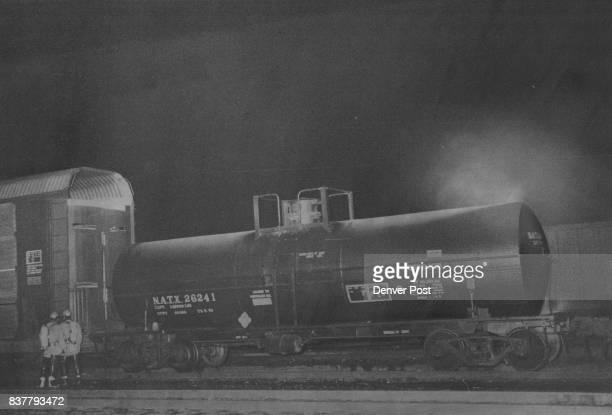 Nitric Acid Leaks From Tank Car Firemen with gas masks uncouple tanker car in Denver Rio Grande Western Railroad yards in Denver after tanker began...