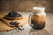 Fresh from the tap nitrous infused dark rich nitro black coffee in a glass jar java creamy beautiful froth foam head lifestyle decor with roasted beans on a rustic reclaimed wood wooden table backgrou