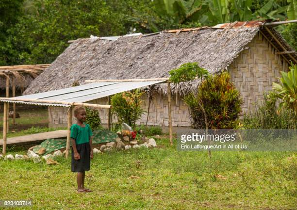 NiVanuatu child in front of a traditional house made with palm leaves and a tomb Shefa Province Efate island Vanuatu on August 25 2007 in Efate...