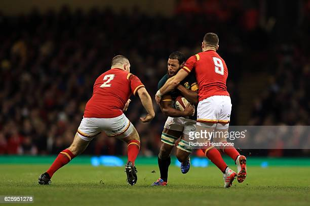 Nizaam Carr of South Africa is tackled by Gareth Davies and Ken Owens of Wales during the international match between Wales and South Africa at...