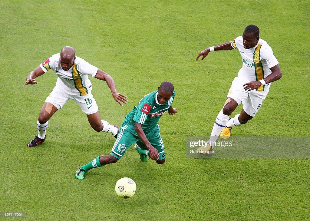 Njabulo Manqana of AmaZulu (C) beats Ramahlwe Mpahlelel of Mamelodi Sundowns to the ball during the Absa Premiership match between AmaZulu and Mamelodi Sundowns at Moses Mabhida Stadium on April 21, 2013 in Durban, South Africa.