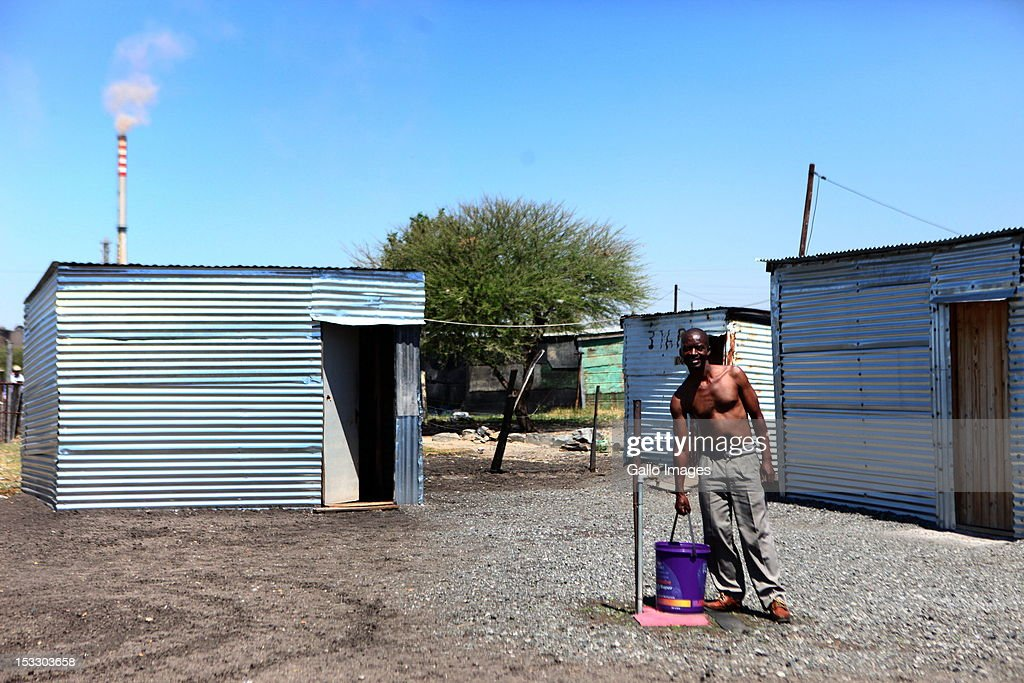 A Nkaneng resident watches as the Marikana Commission of Inquiry visits the area on October 3, 2012 in Rustenberg, South Africa. The Commission which is investigating what led to the deaths of 46 people during a violent wage strike by Lonmin mine workers has been delayed to allow lawyers to speak to the families of the victims.