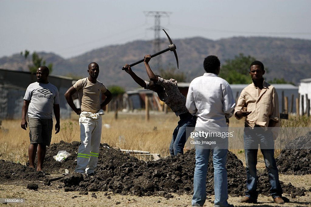 Nkaneng residents dig a grave as the Marikana Commission of Inquiry visits the area on October 3, 2012 in Rustenberg, South Africa. The Commission which is investigating what led to the deaths of 46 people during a violent wage strike by Lonmin mine workers has been delayed to allow lawyers to speak to the families of the victims.