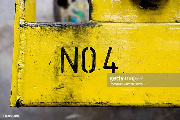No 4 stenciled on yellow metal surface in factory