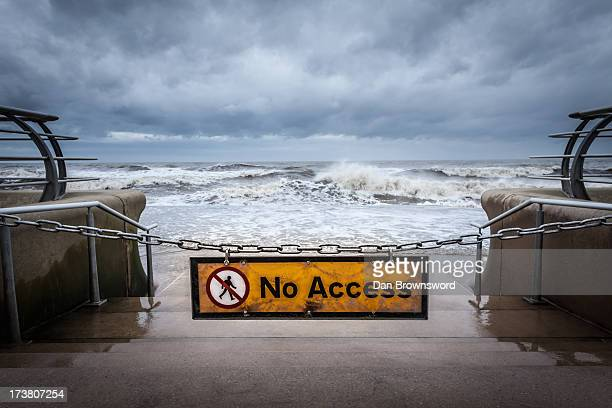 "–No access"" sign at stormy beach"