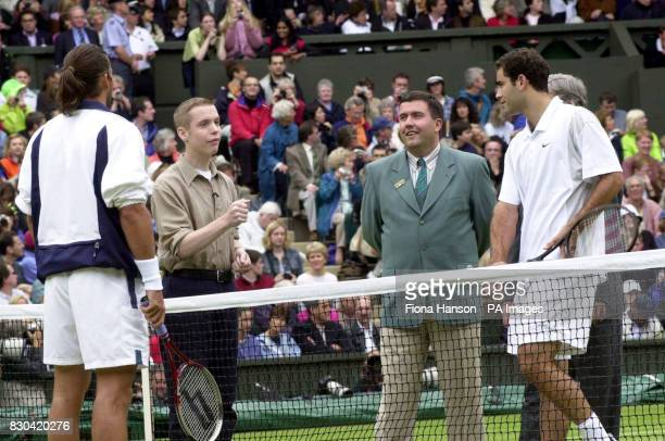 Anthony Mills from Egham in Surrey tosses the coin as tennis stars Pete Sampras and Pat Rafter before the start of the Men's Singles Final at...