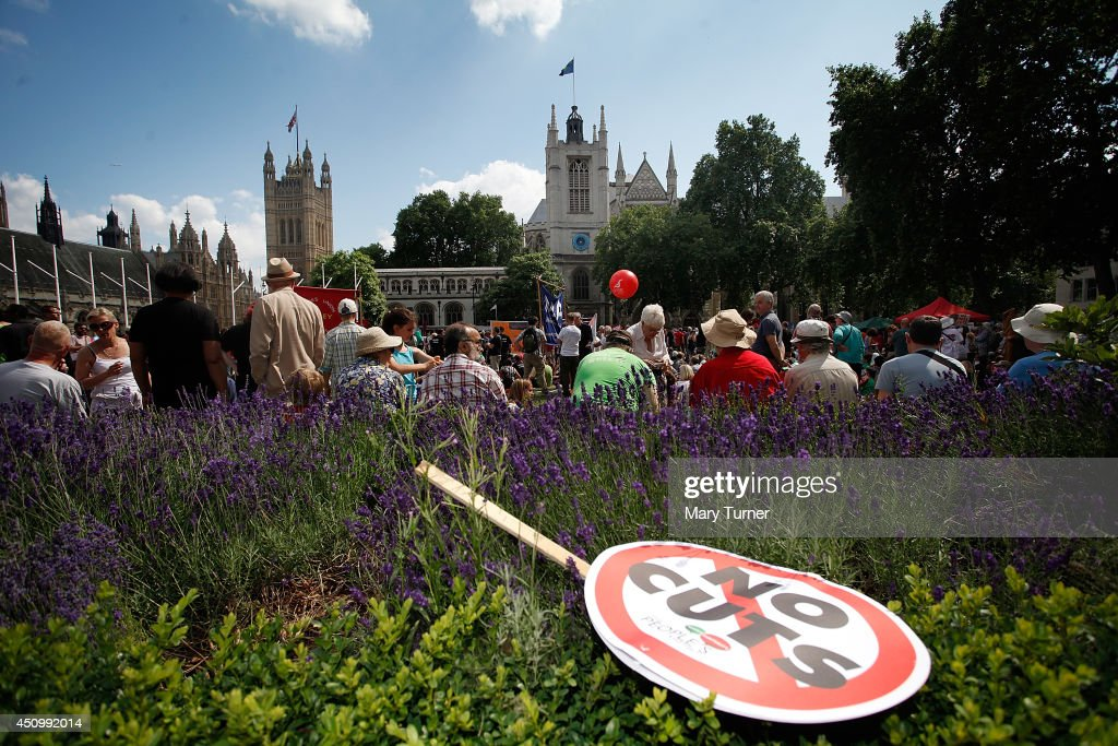 A 'no cuts' placard lies across flowers in Parliament Square where a crowd of demonstrators gathered to protest against the government's austerity cuts on June 21, 2014 in London, England. The crowd of thousands marched from Oxford Circus to Westminster where they listened to speakers including Russell Brand and Diane Abbott MP.
