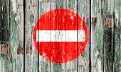 No entry sign painted on an old wooden door with flakey paint