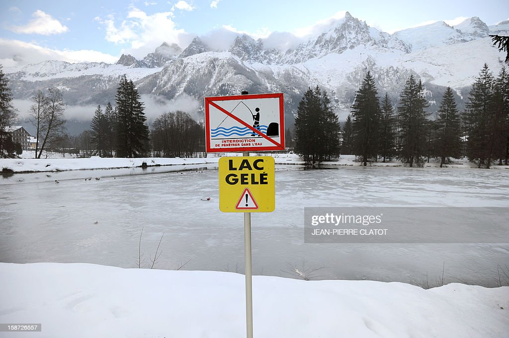 A no fishing and a frozen lack sign are pictured on December 26, 2012 in front of the frozen Gailland lake in the Chamonix valley, French Alps. AFP PHOTO / Jean Pierre Clatot