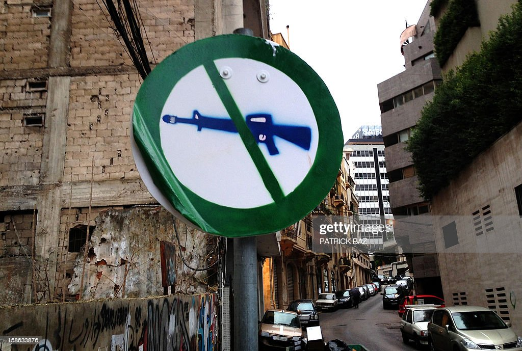 A 'no gun' sign is plastered over a traffic sign in the trendy neighborhood of Gemmayze in the Lebanese capital Beirut on December 22, 2012. AFP PHOTO/PATRICK BAZ