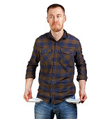 No money concept. Young man in a checkered shirt showing empty pockets, sad unhappy face expression. Isolated on white background