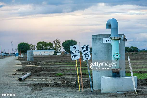 No oilfield traffic sign next to groundwater well with oil well pump jack and cotton field in background Kern County located over the Monterey Shale...