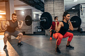 Shot of two young men and a woman lifting weights at the gym