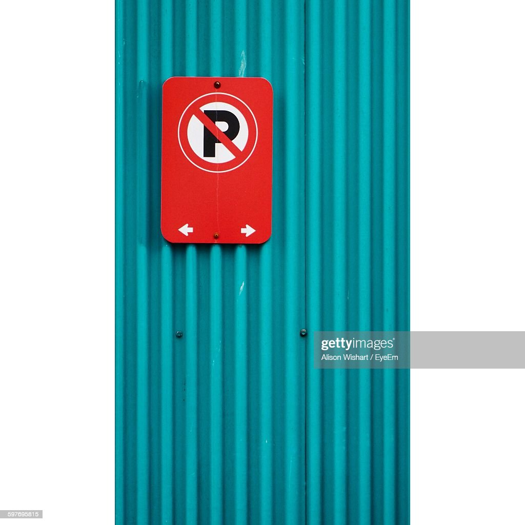 No Parking Sign On Corrugated Iron Against White Background