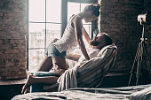 Young passionate couple looking on each other while spending free time at home