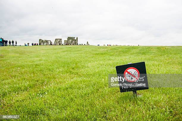 No Smoking Sign On Grassy Landscape Against Cloudy Sky