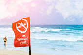 No swimming danger sign at the beach, warning sign at the beach with people swim, caution no swimming allowed.