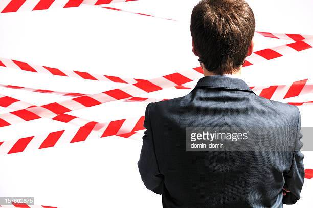 No trespassing, man against safety tape background, rear view