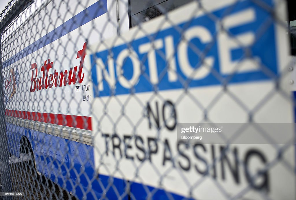 A 'No Trespassing' sign hangs on a fence as delivery trucks sit outside an idled Hostess Brands Inc. bakery in Peoria, Illinois, U.S., on Wednesday, Feb. 27, 2013. Flowers Foods Inc., maker of packaged bakery foods, won the bidding for the majority of the bread-making business of Hostess Brands Inc., including the Wonder, Butternut, Home Pride, Merita and Nature's Pride brands, 20 bread plants, 38 depots and other assets, after no other competing offers were submitted. Photographer: Daniel Acker/Bloomberg via Getty Images