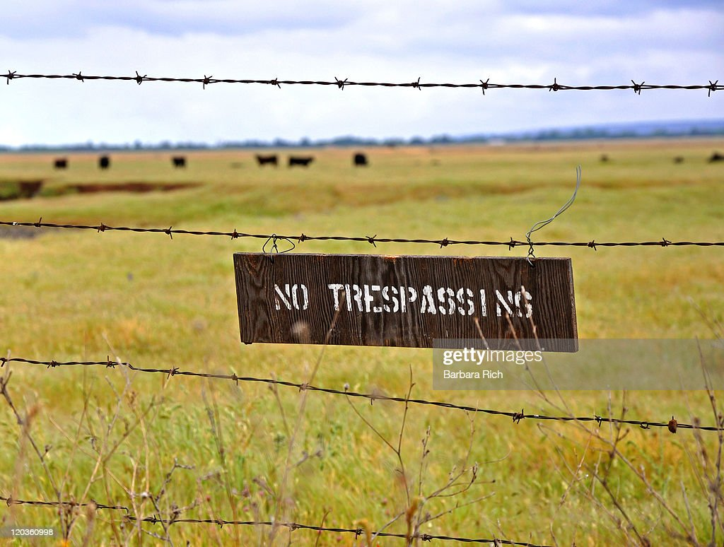 No trespassing sign on barbed wire fence