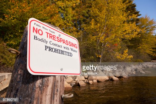 No Trespassing warning sign on a tree stump at the lakeside : Stock Photo