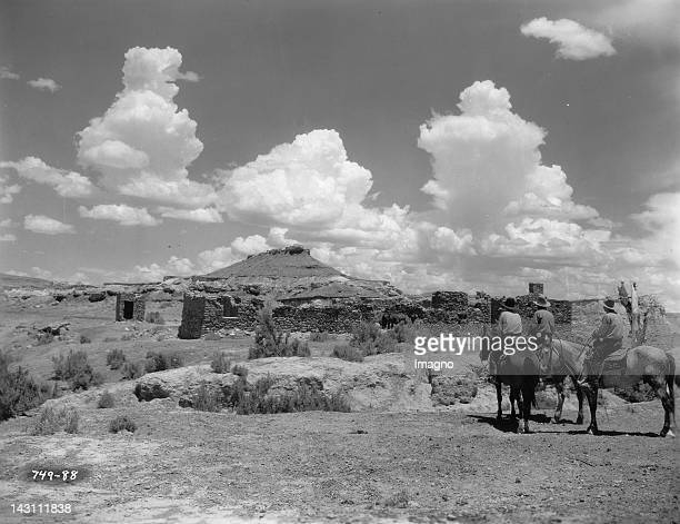 Noah Beery Jr and two riders inspect the ruins of an Indian trading post on the rim of Blue Canyon in the Painted Desert in the film 'Stormy' Arizona...