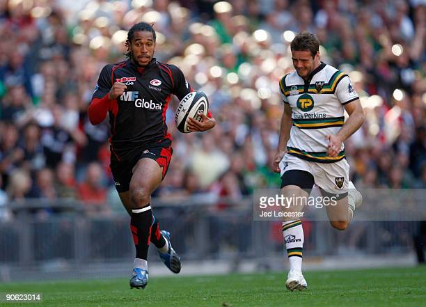 Noah Cato of Saracens runs away from Ben Foden of Northampton Saints to score a breakaway try during the Guinness Premiership match between Saracens...
