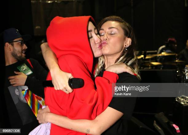 Noah Cyrus and Miley Cyrus kiss as they greet each other backstage during the 2017 BLI Summer Jam at Nikon at Jones Beach Theater on June 16 2017 in...
