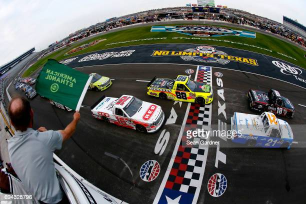 Noah Gragson driver of the Switch Toyota and Johnny Sauter driver of the Allegiant Travel Chevrolet lead the field at the start of the NASCAR Camping...