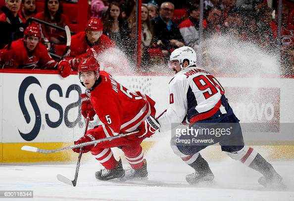 Noah Hanifin of the Carolina Hurricanes and Marcus Johansson of the Washington Capitals skate for position on the ice during overtime of an NHL game...