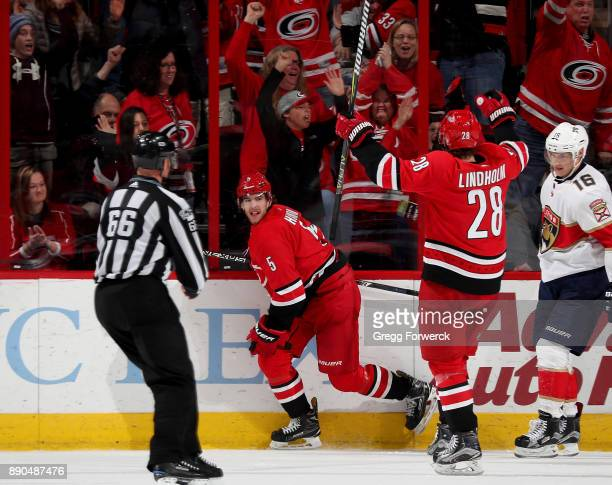 Noah Hanifin of the Carolina Hurricanes celebrates a game winning goal with teammate Elias Lindholm during overtime against the Florida Panthers...