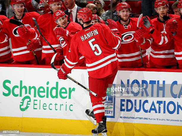 Noah Hanifin of the Carolina Hurricanes celebrates with teammates after scoring his first NHL goal during a NHL game against the Anaheim Ducks at PNC...