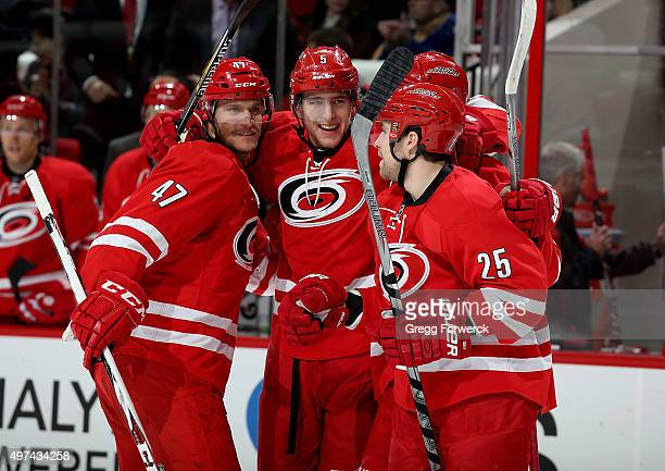 Noah Hanifin of the Carolina Hurricanes celebrates with teammates Michal Jordan and Chris Terry after scoring his first NHL goal during a NHL game...
