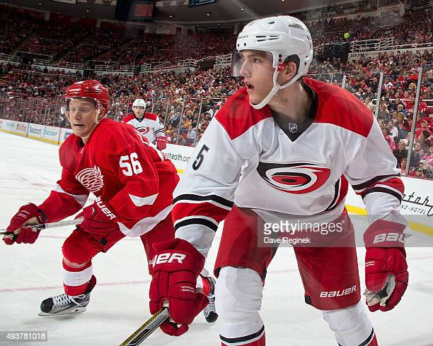 Noah Hanifin of the Carolina Hurricanes follows the play next to Teemu Pulkkinen of the Detroit Red Wings during an NHL game at Joe Louis Arena on...