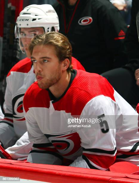 Noah Hanifin of the Carolina Hurricanes looks on from the bench prior to puck drop against the Winnipeg Jets at the Bell MTS Place on October 14 2017...