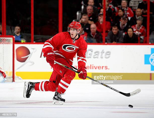 Noah Hanifin of the Carolina Hurricanes looks to settle a loose puck during a NHL game against the Florida Panthers at PNC Arena on October 13 2015...