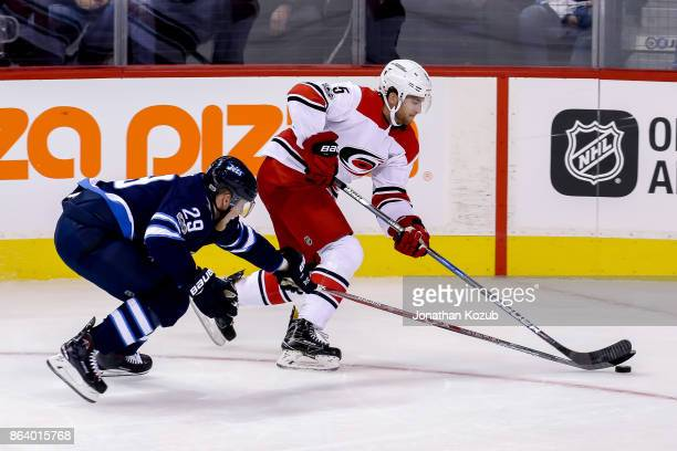 Noah Hanifin of the Carolina Hurricanes plays the puck away from Patrik Laine of the Winnipeg Jets during third period action at the Bell MTS Place...