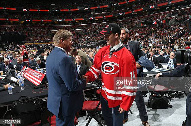 Noah Hanifin shakws the hand of a member of the Carolina Hurricanes after being selected fifth overall by the Carolina Hurricanes during Round One of...