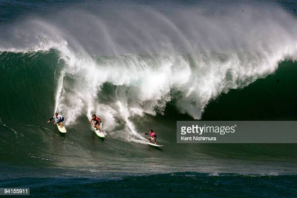 Noah Johnson Kohl Christensen and Ibon Amatrian ride a wave during the first round of the Quiksilver in Memory of Eddie Aikau Competition big wave...