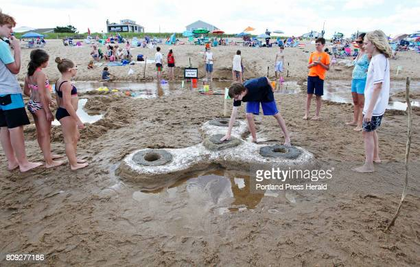 Noah Luke of Mass smoothes out a spot on a Fidget Spinner creation during the 31st annual Ocean Park Sand Sculpture Competition At right are James...