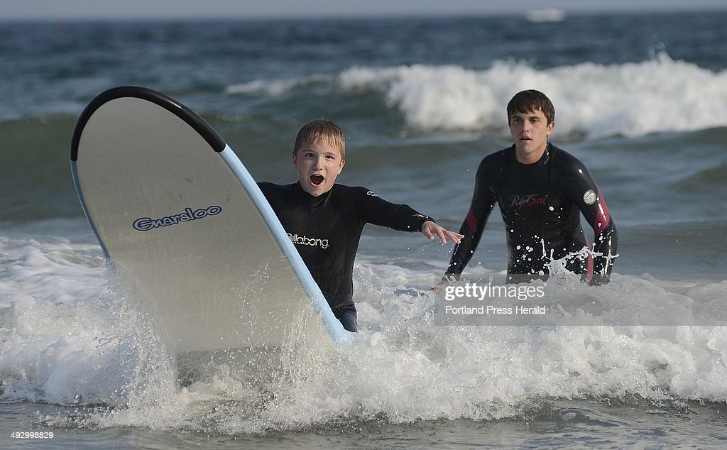 Noah Rassier 12 of Milford New Hampshire reacts as rides a wave during Special Surfer Night in Kennebunk Tuesday July 17 2012 Looking on is volunteer...