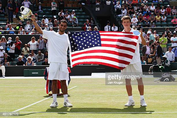 Noah Rubin of the United States and Stefan Kozlov of the United States hold aloft a USA flag as they celebrate with their respective trophies after...
