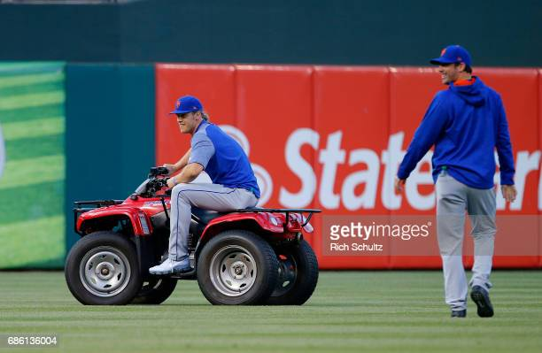 Noah Syndergaard of the New York Mets steals the Phillie Phanatic's ATV as teammate Matt Harvey looks on before a game against the Philadelphia...