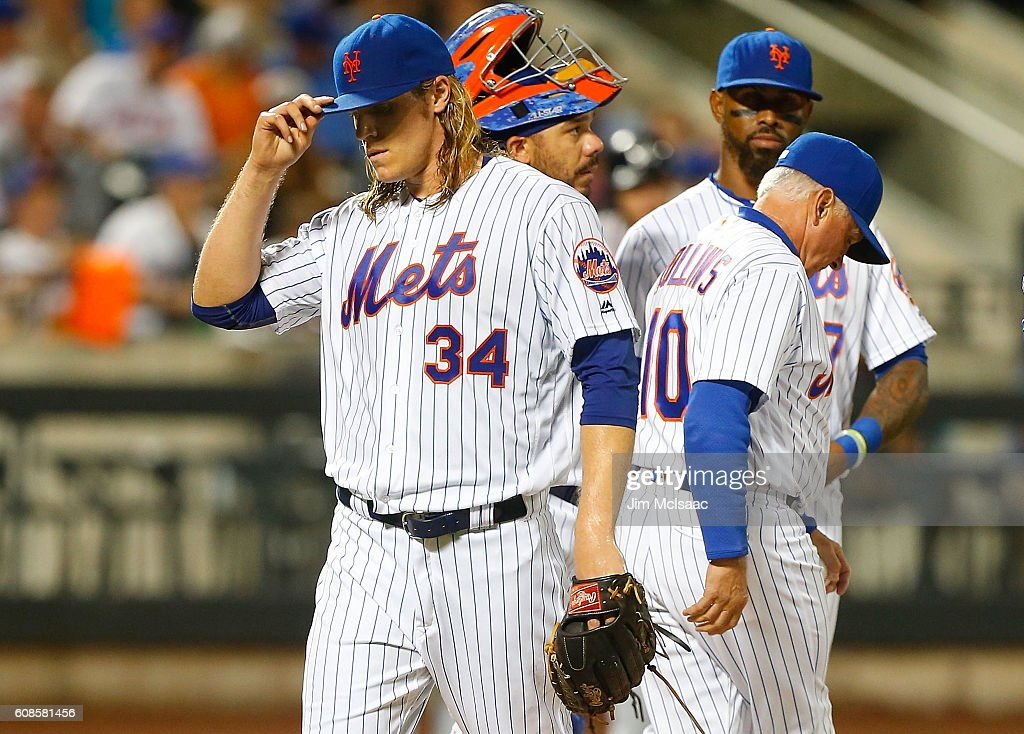 Noah Syndergaard #34 of the New York Mets walks to the dugout in the fourth inning after being removed from a game against the Atlanta Braves by manager Terry Collins #10 at Citi Field on September 19, 2016 in the Flushing neighborhood of the Queens borough of New York City.